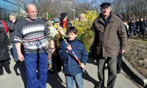 Raoul Biedinger (10) Vertreibt mit der Rassel den Winter: Außerdem tragen Uve Laabs und Rudolf Mütschow eine mit Blüten und Blumen von den Mitarbeitern geschmückte Bank an ihrem Platz. Foto: Joachim Kloock