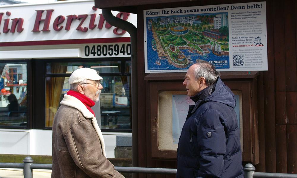 Hansi Parczyk und Rainer Möller vor der Schautafel am Alten Strom in Warnemünde