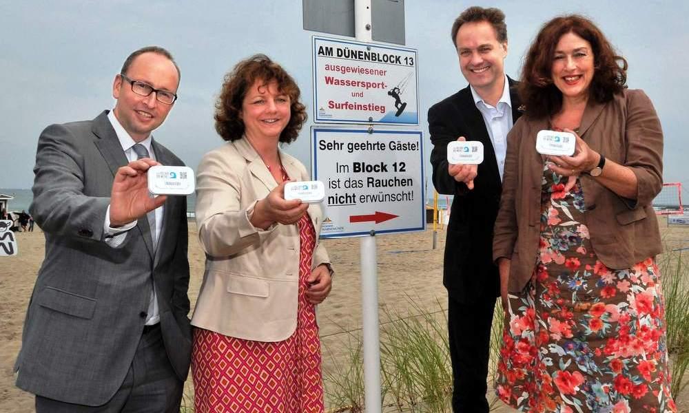 Matthias Fromm, Anett Bierholz, Holger Matthäus und Dr. Monika Griefahn präsentieren  en Strandascher in Warnemünde. Foto: Joachim Kloock