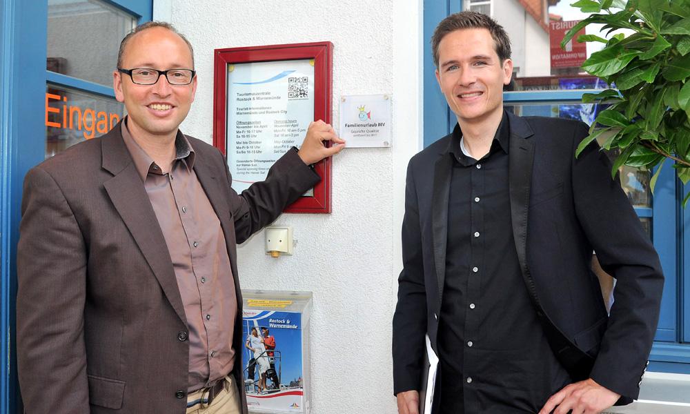 Tourismusdirektor Matthias Fromm und Sachgebietsleiter Johannes Wolff montierten das neue Qualitätssiegel an die Tourist-Information in Warnemünde an. Foto: Joachim Kloock