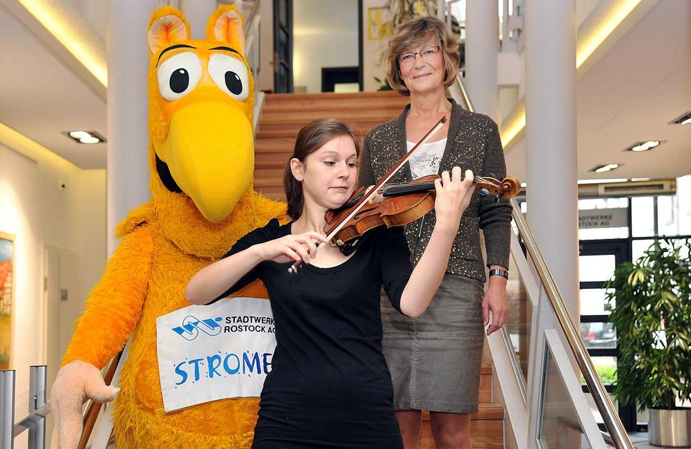 HMT-Studentin Laura Kania (22) an der Violine mit Ute Römer (Vorstand SWRAG) und Stadtwerke-Maskottchen Stromer auf der Treppe im Haus der Stadtwerke. Foto: Joachim Kloock