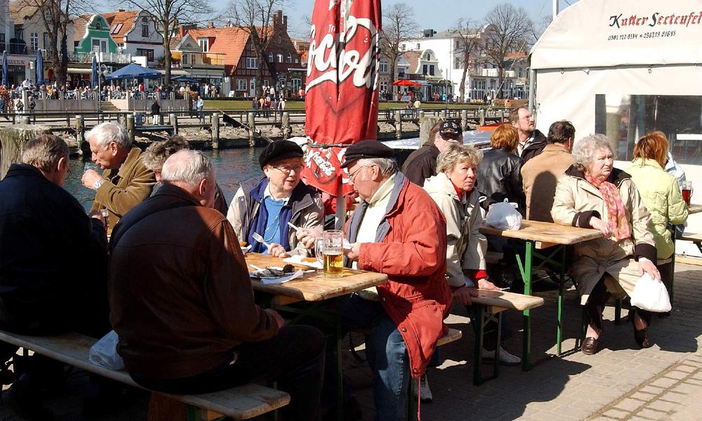 Heringsessen auf dem Fischmarkt Warnemünde. Foto: Joachim Kloock