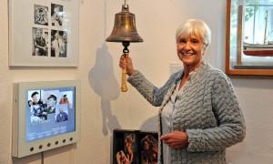 """Witwe Gabriele Köbbert an der Original Glocke aus """"Klock 8, achtern Strom"""" im Heimatmuseum Warnemünde. Foto: Joachim Kloock"""
