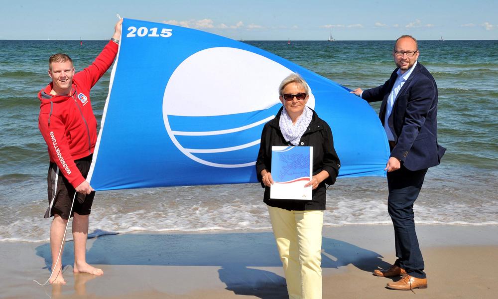 Tony Wilken (DRK Wasserwacht), Ursula Klause und Tourismusdirektor Matthias Fromm (beide Tourismuszentrale Rostock & Warnemünde) freuen sich über die erneute Auszeichnung mit der Blauen Flagge. Foto: Joachim Kloock